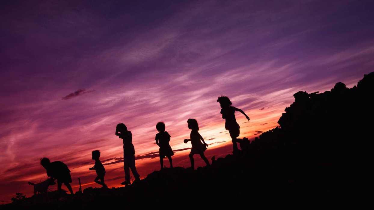 Des enfants avec un coucher de soleil rouge en fond