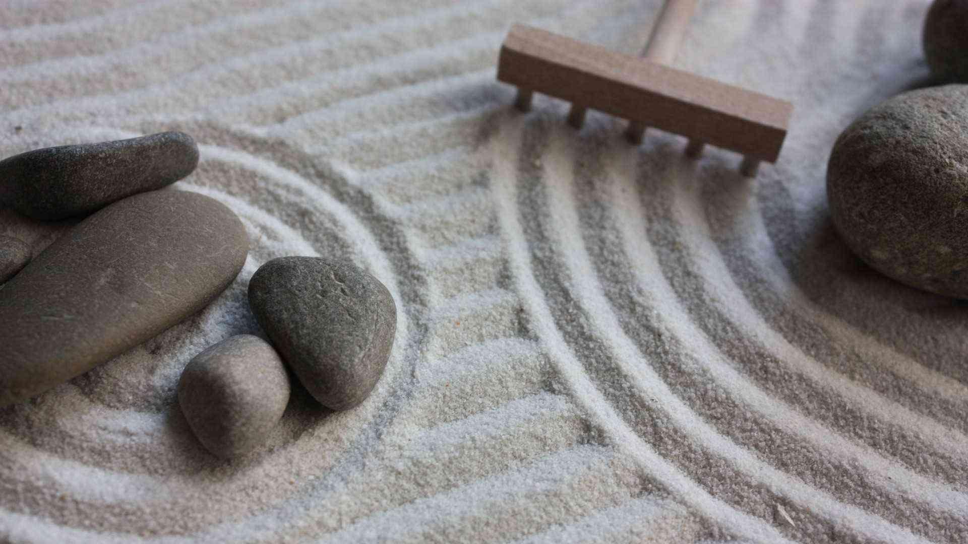 Petits galets posés dans du sable avec un râteau à coté