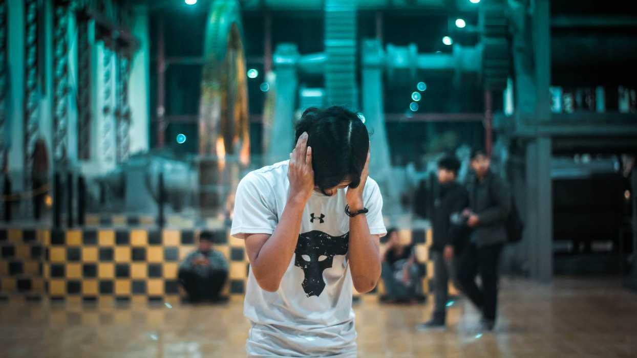 Un jeune se bouche les oreilles avec ses mains